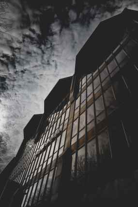 brown concrete building with glass window under gray sky